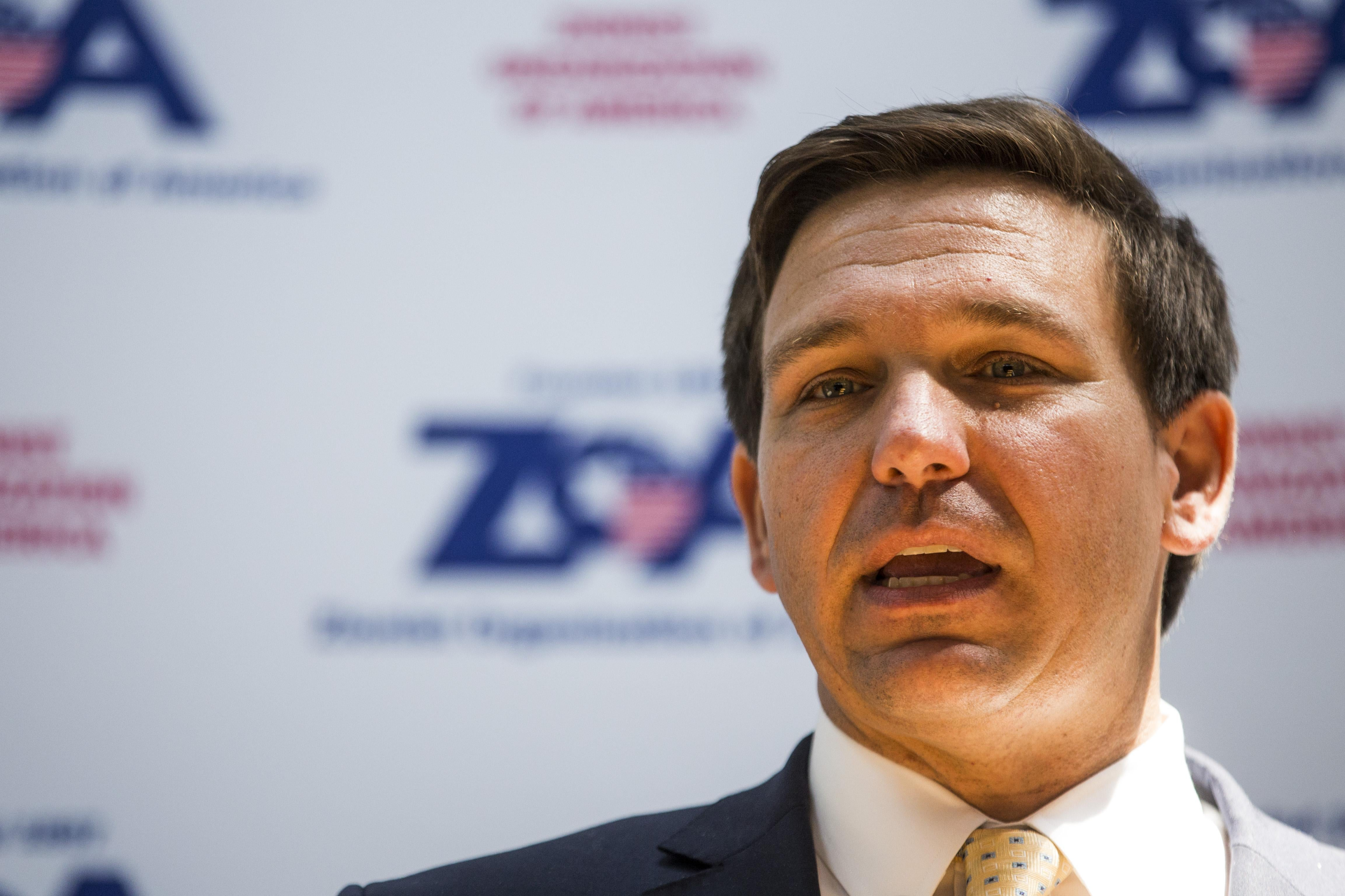 Florida Rep. Ron DeSantis speaking in front of a banner for the Zionist Organization of America.