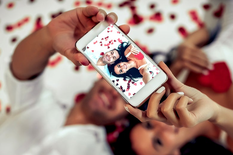 A couple lying on a bed taking a selfie