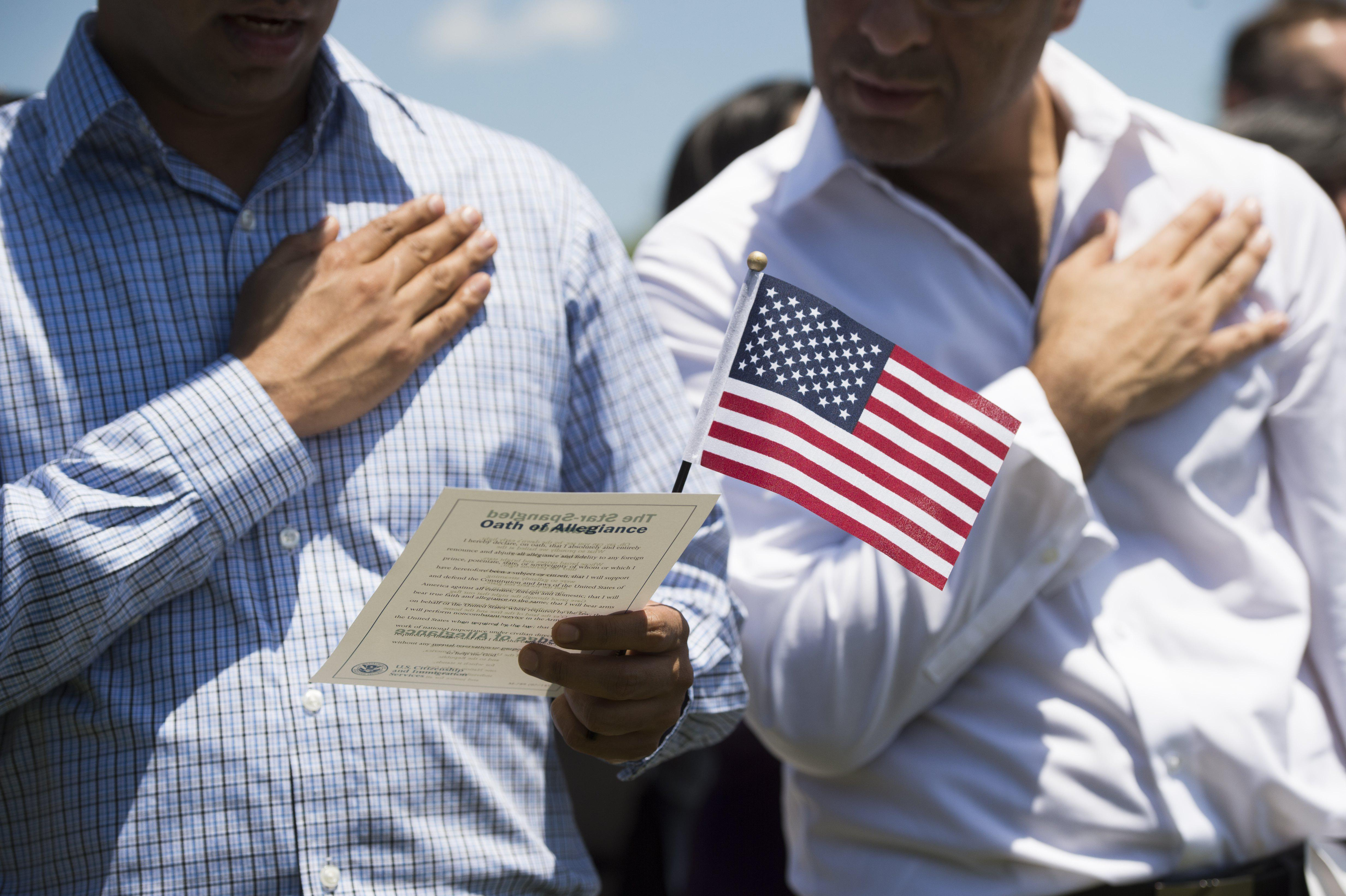 Newly sworn-in U.S. citizens recite the Pledge of Allegiance during a 2017 naturalization ceremony at Mount Vernon, Virginia.