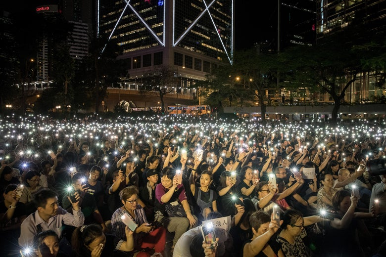 A huge crowd of protesters waving their mobile phones in the air outside at night.