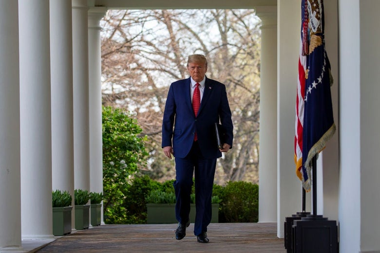 Trump strides purposefully down a walkway outside the White House.