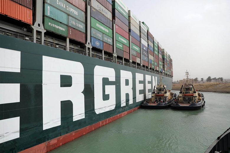 Two small boats next to a giant container ship in the Suez Canal