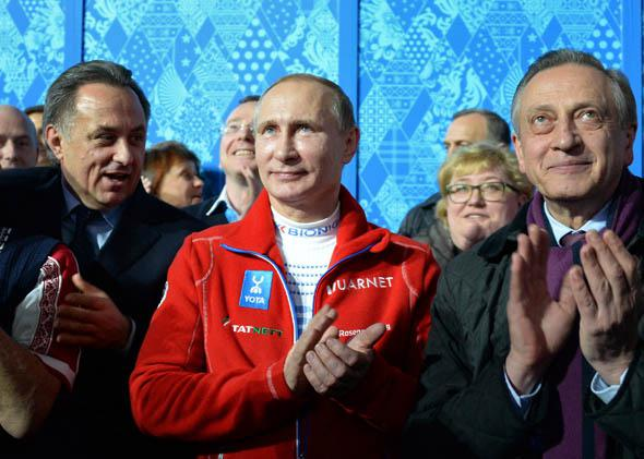 Russia's President Vladimir Putin applauds as team Russia won the gold medal during the Figure Skating Team Flower Ceremony at the Sochi Winter Olympics.