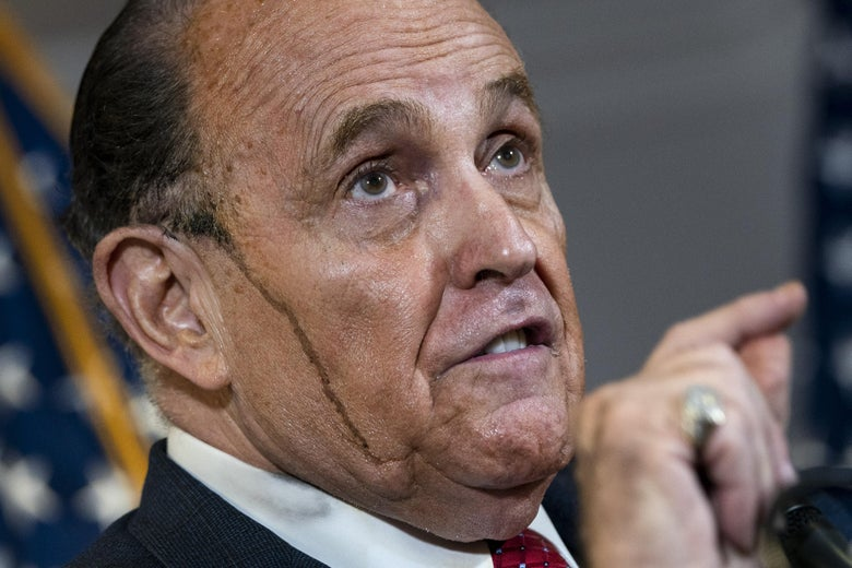 Hair coloring appears to drip down the side of Rudy Giuliani's face as he speaks and points during the press conference