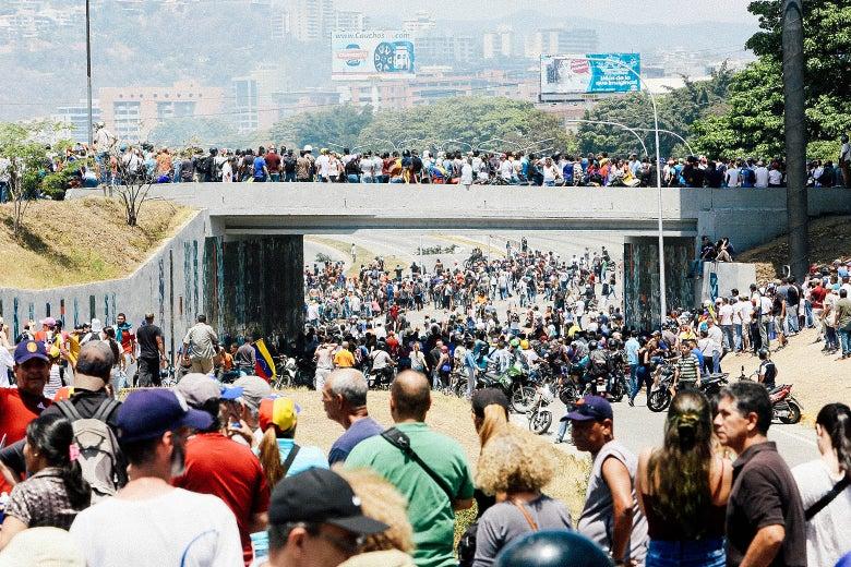 Supporters of Venezuelan opposition leader Juan Guaido gather near La Carlota Air Base.