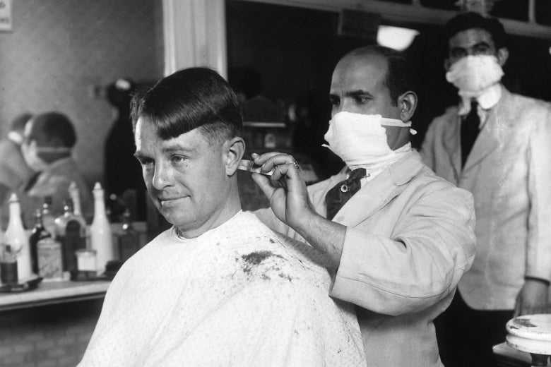 A barber wearing a cloth mask cuts a man's hair