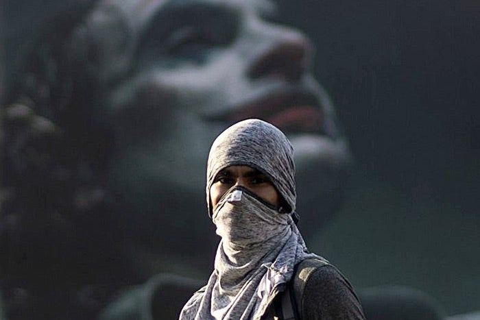 A Chilean protester stands in front of a mural of the Joker.