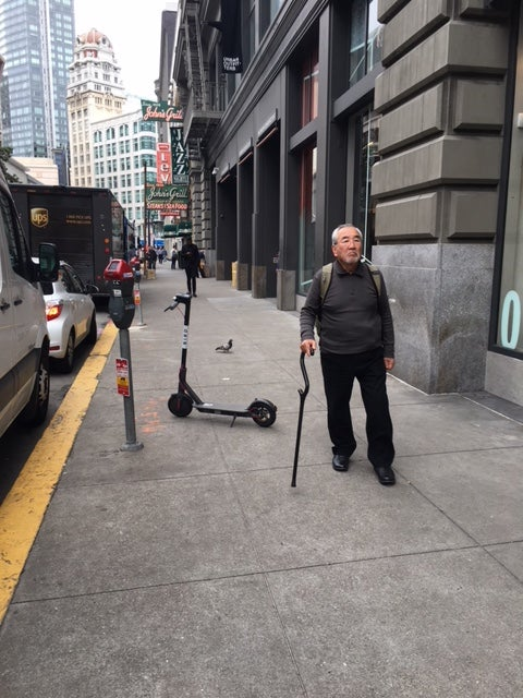 An older man dodges a scooter downtown.