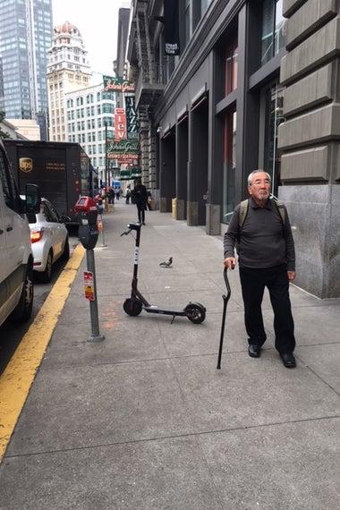An older man dodges a scooter downtown.