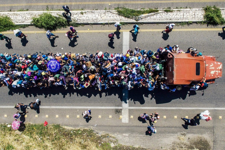 Honduran migrants onboard a truck as they take part in a caravan heading to the U.S.