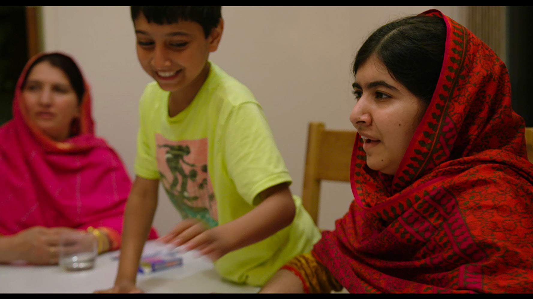 Malala Yousafzai. In the background, a young boy smiles.