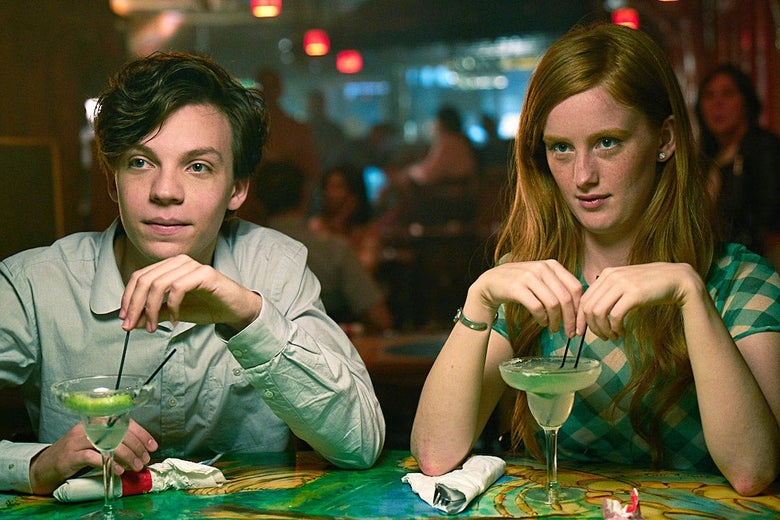 Nicholas Alexander and Bobbi Salvör Menuez sit at a table drinking out of cocktail glasses in this still from Adam.