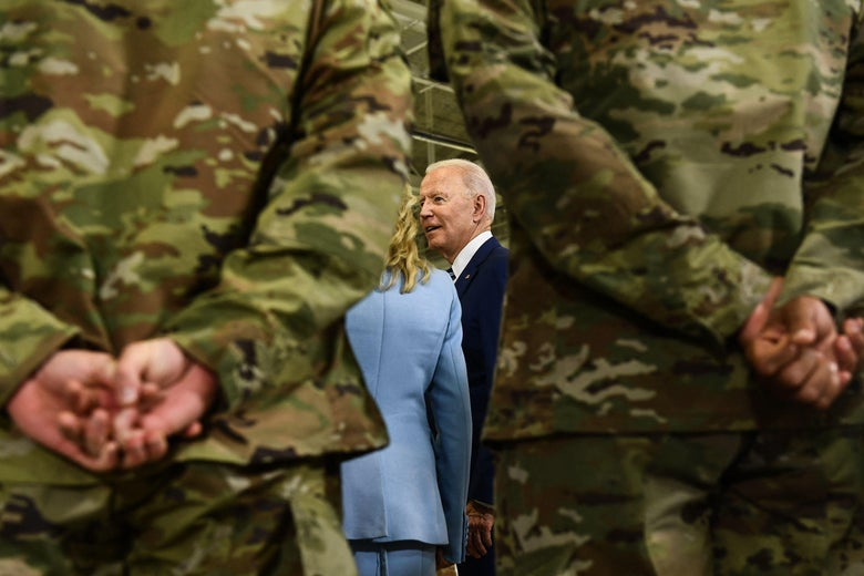 Low angle shot of Biden seen between two military personnel in uniform standing with hands clasped behind their backs