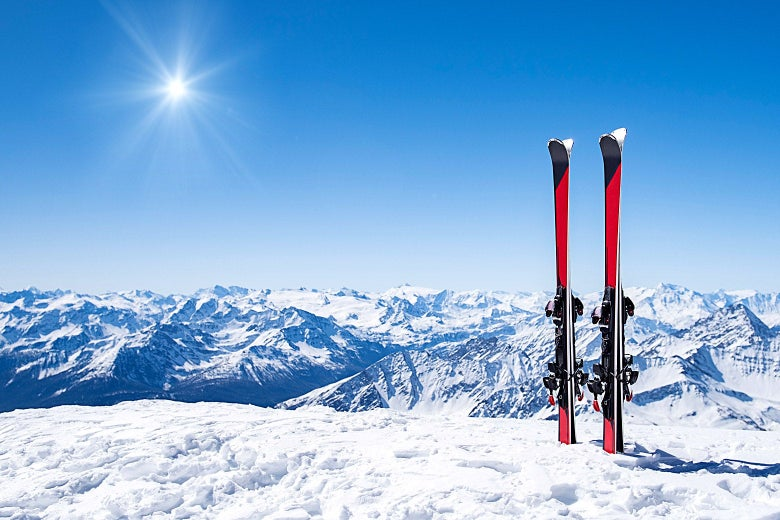 Two pairs of skis are seen standing upright near the edge of a snowy hill.