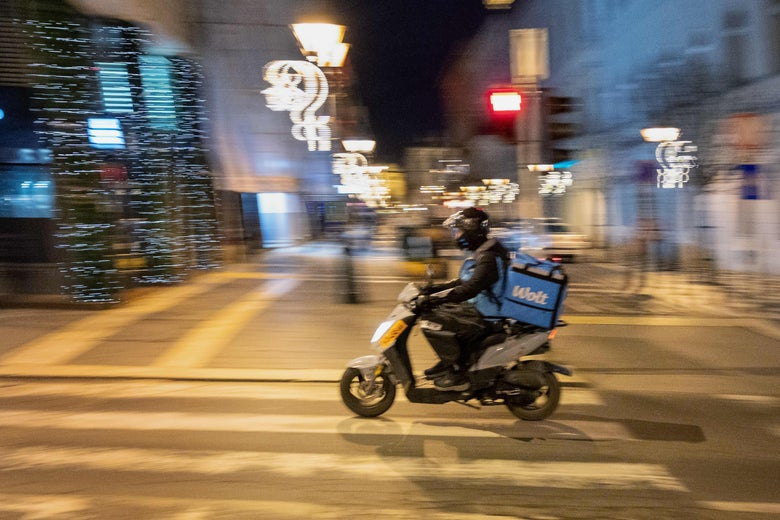 A food delivery bike courier blurred in motion through an empty street