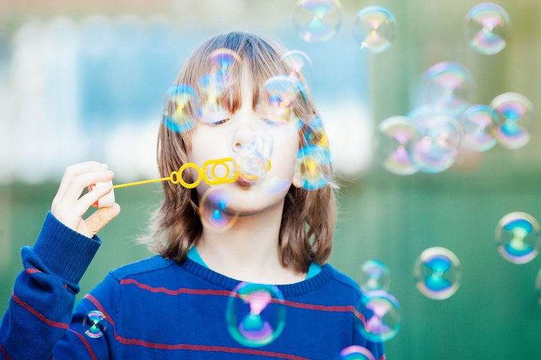 A child with long hair blows bubbles.