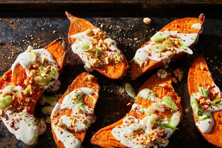 Six roasted sweet potato halves drizzled with maple crème fraîche dressing, scallions, peanuts, chile flakes, and lime zest.