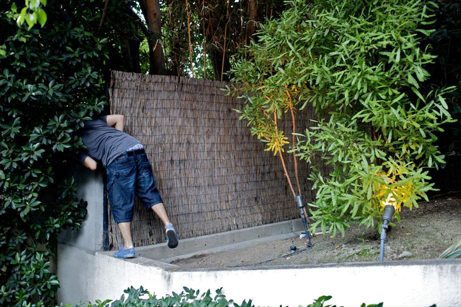Ben looks for a car behind the wall of a celebrity's home in Los Angeles, Aug. 5, 2009.