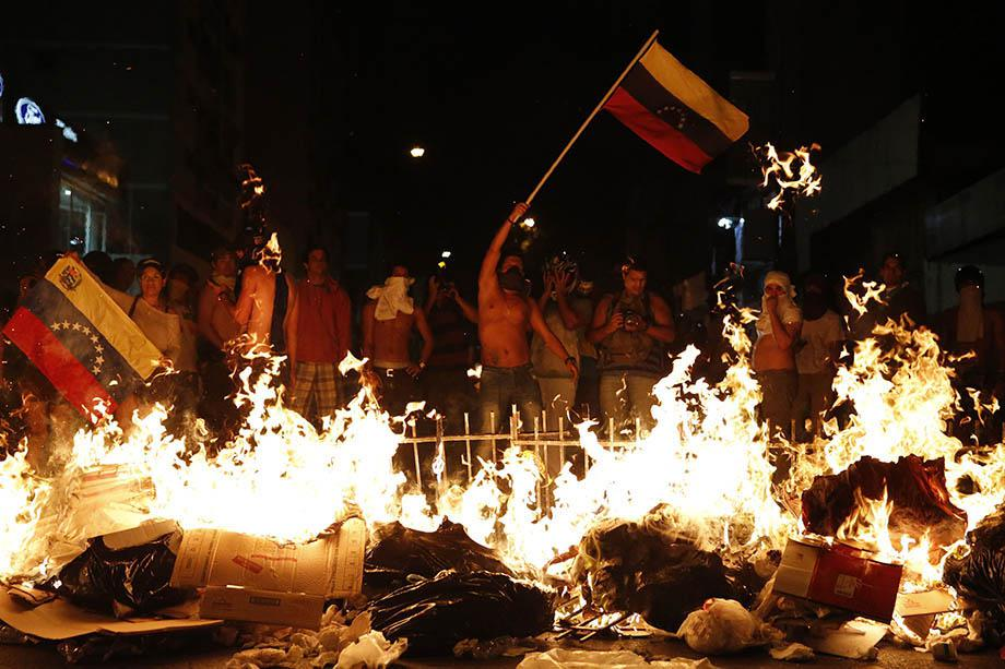 Opposition demonstrators hold a Venezuelan flag in front of a burning barricade during a protest against President Nicolas Maduro's government in Caracas.