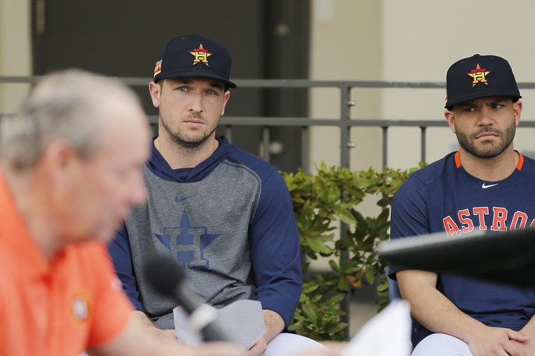 Alex Bregman and Jose Altuve, in warm ups and baseball hats, look on somewhat skeptically as Jim Crane reads seated at a table in front of a microphone in the foreground.