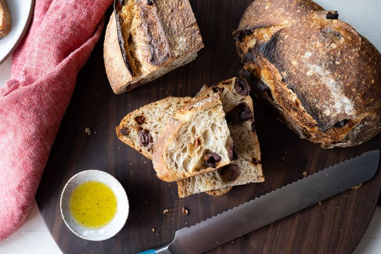 On a sleek wooden cutting board, a whole loaf of bread next to a stack of sliced bread with olives. Nearby, a small bowl of bright yellow olive oil, flecked with spices.