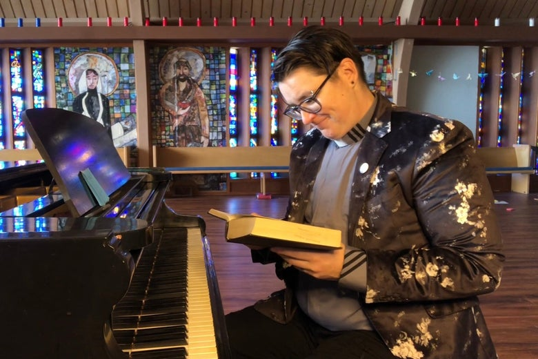 Megan Rohrer sits at a piano and smiles as they look down at a Bible in their hands