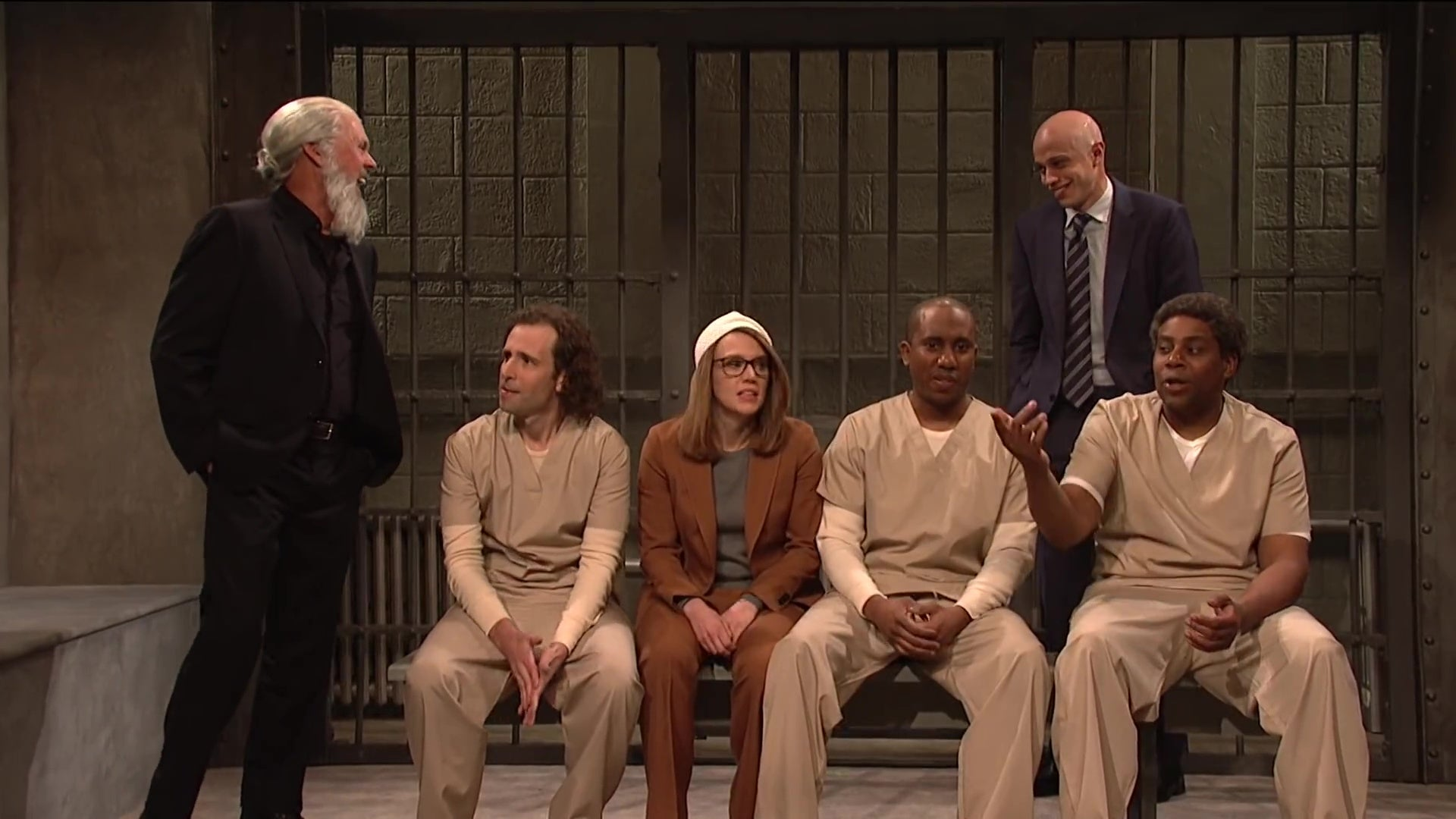 Michael Keaton, as Julian Assange, brags to Kate McKinnon's Lori Loughlin, Pete Davidson's Michael Avenatti, and inmates played by Kyle Mooney, Chris Redd, and Kenan Thompson in a still from SNL.