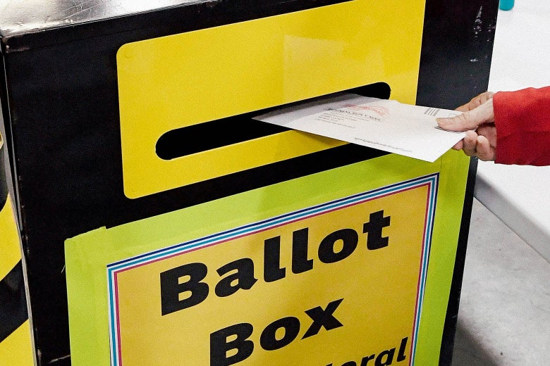 A hand puts an envelope in a box that says Ballot Box.