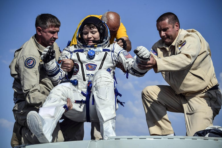 Ground personnel help NASA astronaut Anne McClain to get out of the Soyuz MS-11 capsule shortly after landing in a remote area outside the town of Dzhezkazgan, Kazakhstan, on June 25, 2019.