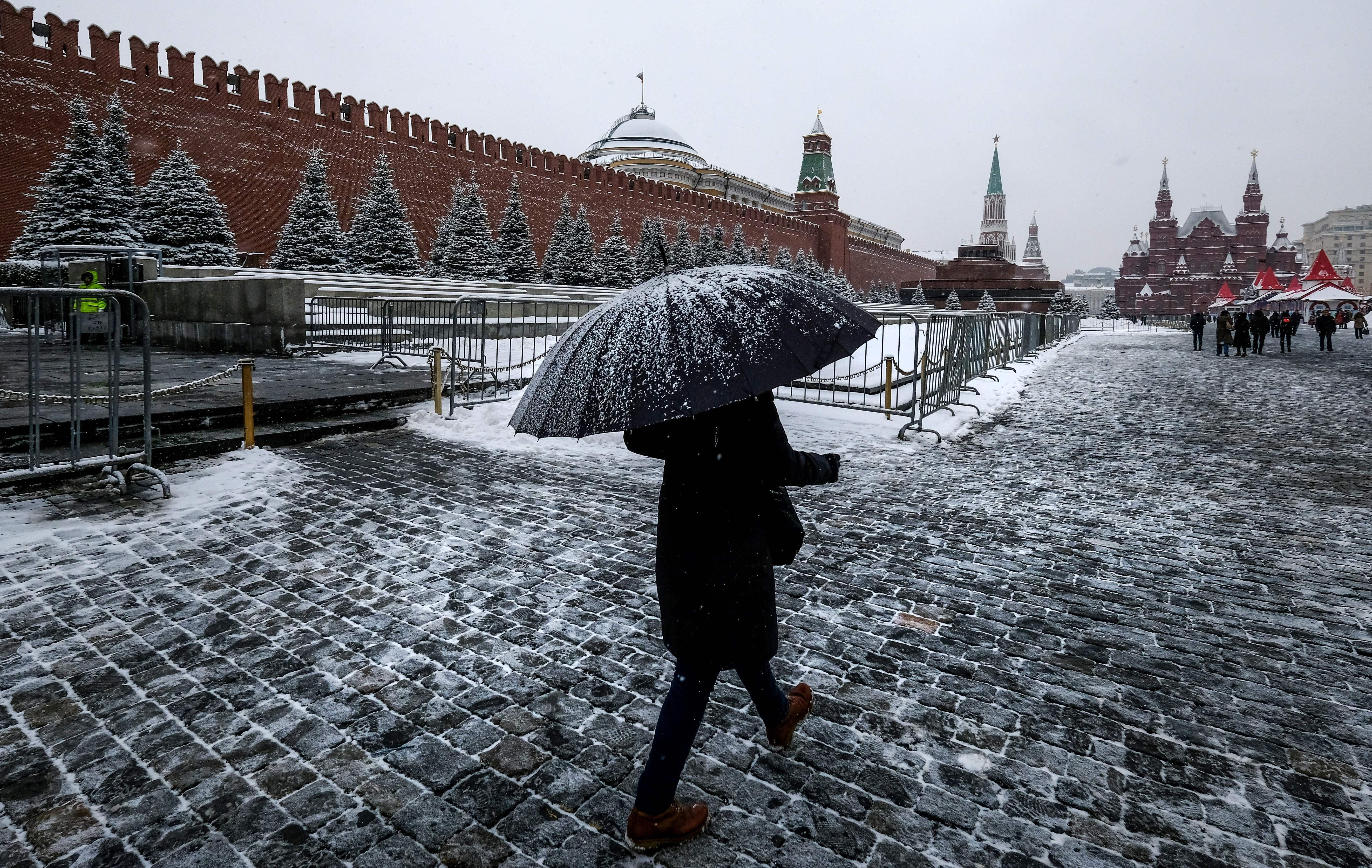 A woman with an umbrella walks on Red Square past the Kremlin after a night of heavy snowfall.