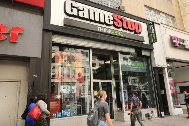 People walk by a GameStop storefront.