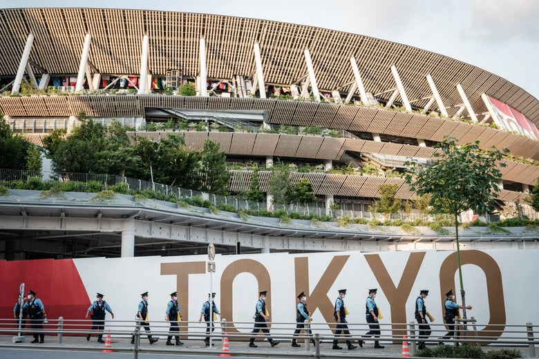 Police officers move towards their position ahead of the opening ceremony of the Tokyo 2020 Olympic Games near the Olympic Stadium in Tokyo on July 23, 2021. (Photo by Yasuyoshi CHIBA / AFP) (Photo by YASUYOSHI CHIBA/AFP via Getty Images)