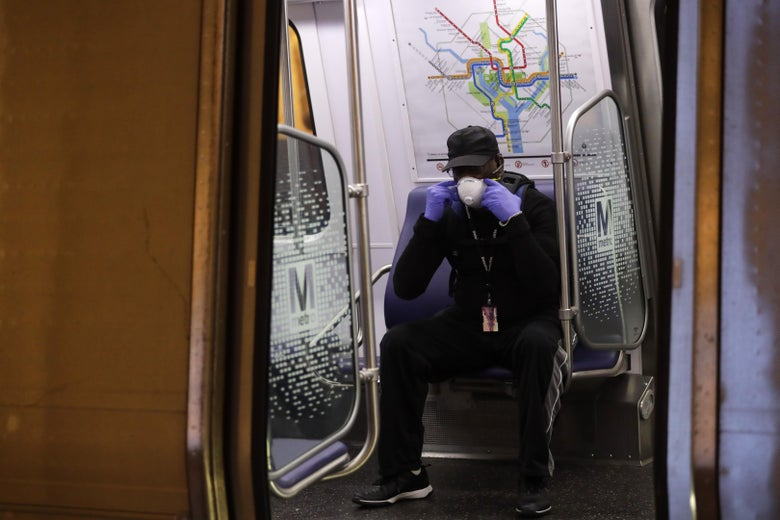 A passenger adjusts his mask in a Metro train car.