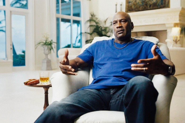 Michael Jordan sits in a chair and gesticulates.