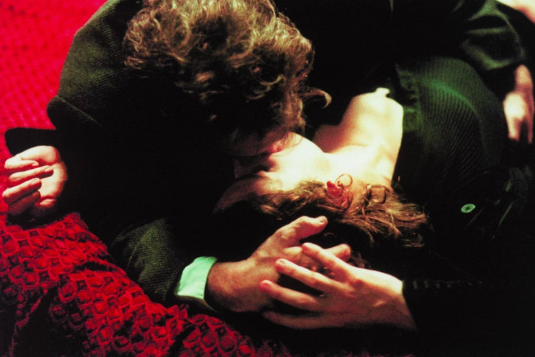 Man kissing woman on a red blanket.