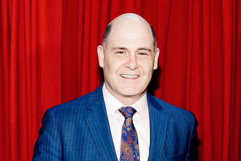Matthew Weiner poses in front of a red curtain.