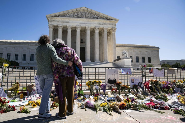 Women embrace in front of a makeshift memorial of flowers for late Supreme Court Justice Ruth Bader Ginsburg