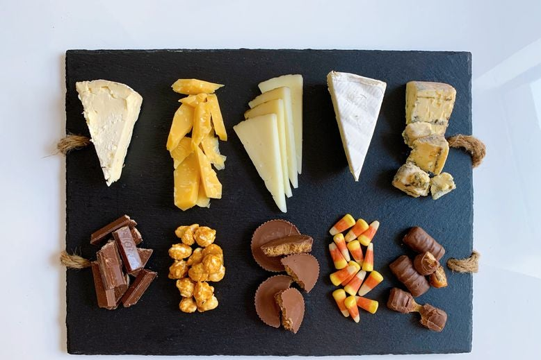 Pairs of blue cheese and Twix, brie and candy corn, manchego and Reese's, Gouda and caramel popcorn, and triple-cream cheese and Kit Kats, arranged on a serving board