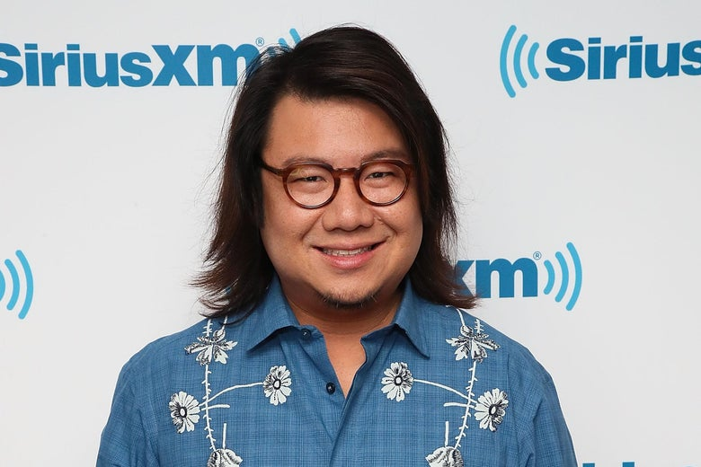 Kevin Kwan, wearing a blue shirt with white flowers and black glasses, stands and smiles at the camera.