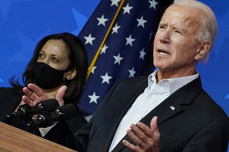 Biden speaks with a masked Harris and a flag behind him.