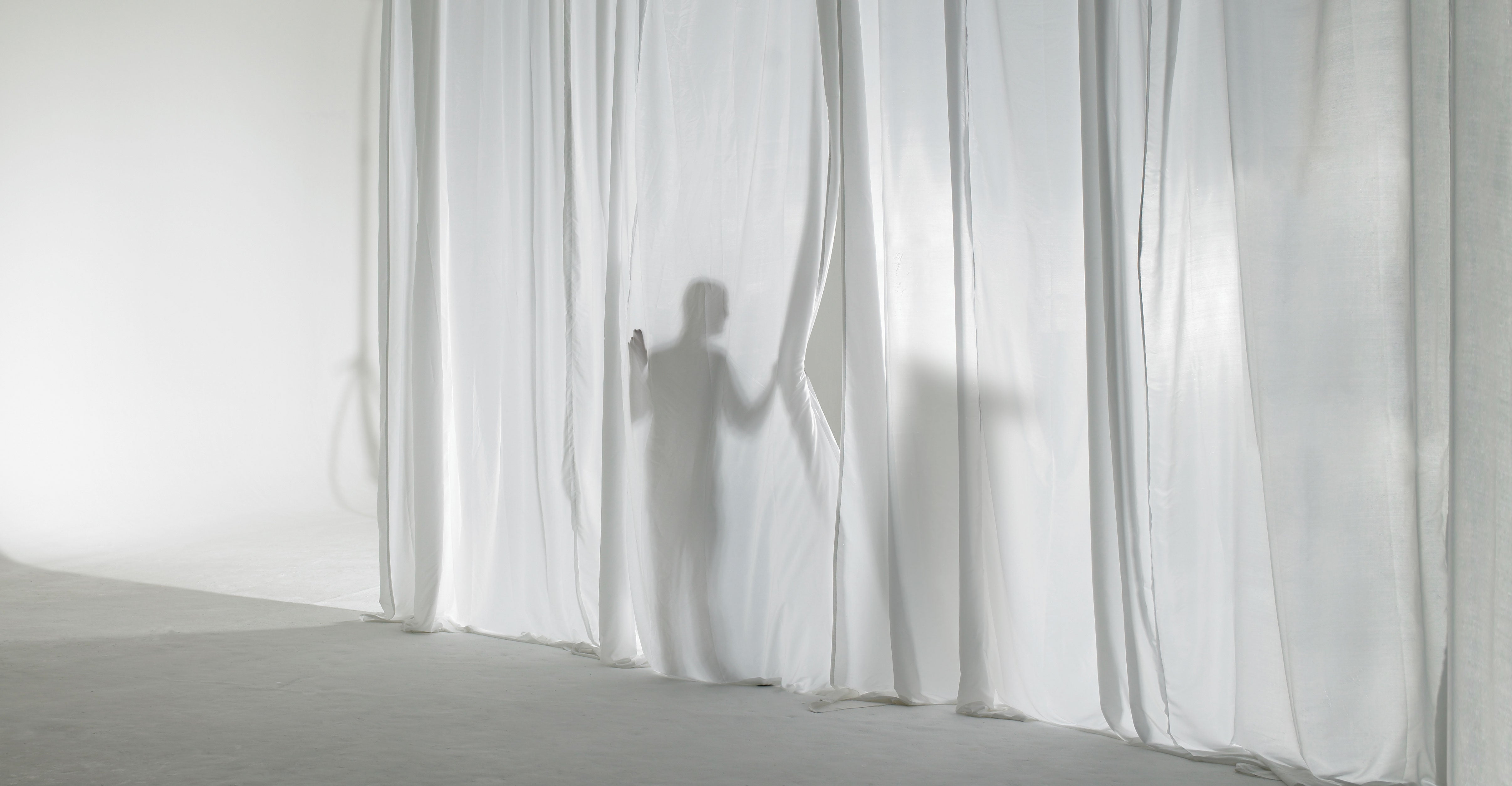 A silhouette of a man and an object can be seen on a curtain that's beginning to be pulled back.
