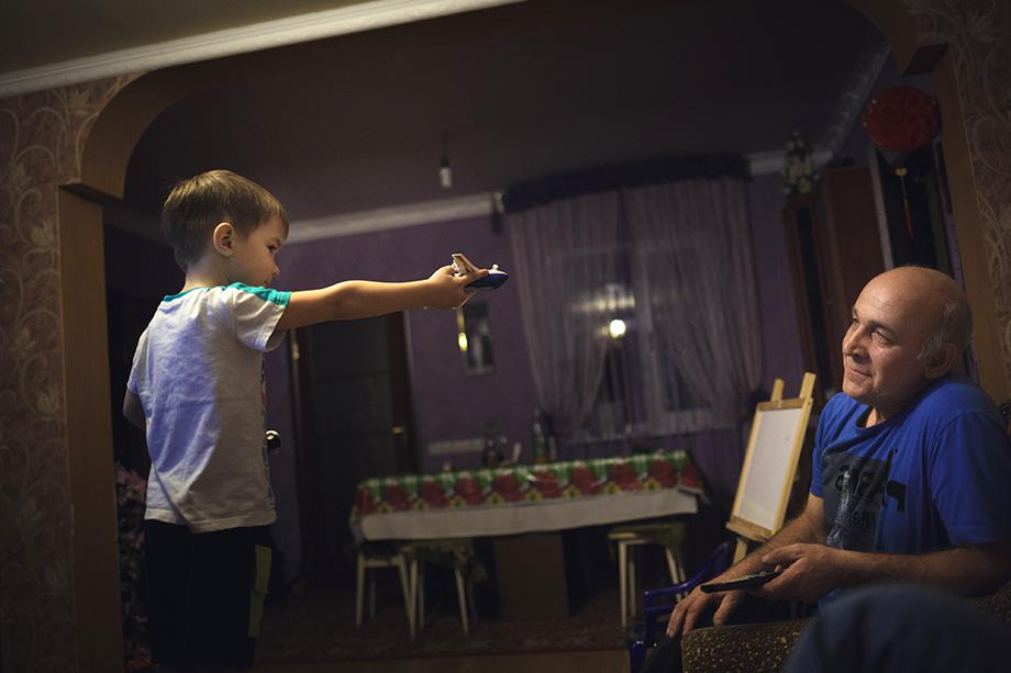 Danila plays with his planes at home with grandfather Aleksander Kovalenko.