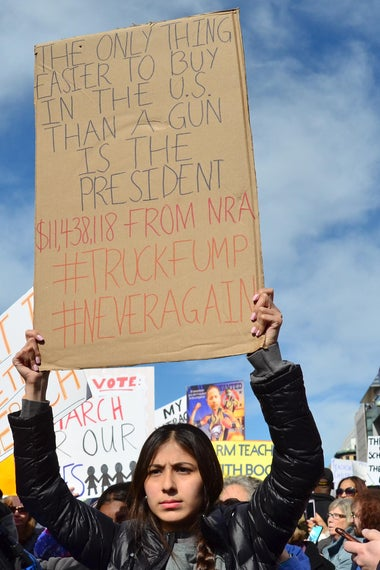 "A woman hoists a poster reading, ""The only thing easier to buy in the U.S. than a gun is the president."""