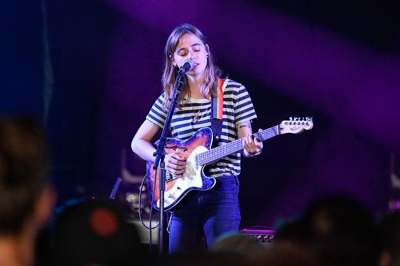 A young white woman with shoulder-length hair plays guitar and sings into a microphone.
