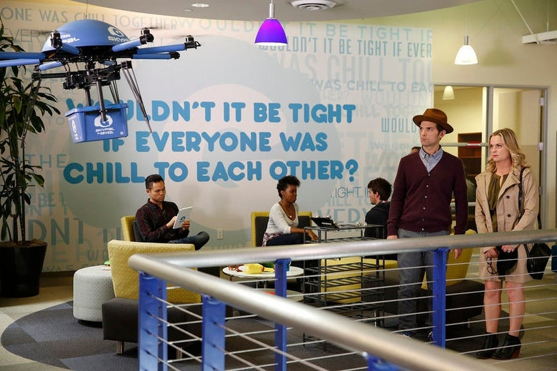 "Ben (Adam Scott) and Leslie (Amy Poehler) stand in an office with a drone flying, in front of a sign that says, ""Wouldn't It Be Tight If Everyone Was Chill to Each Other?"""