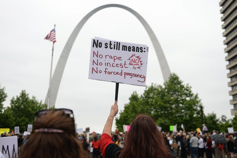A demonstrator displays a sign during an abortion rights rally in front of the Gateway Arch in St. Louis, Missouri.