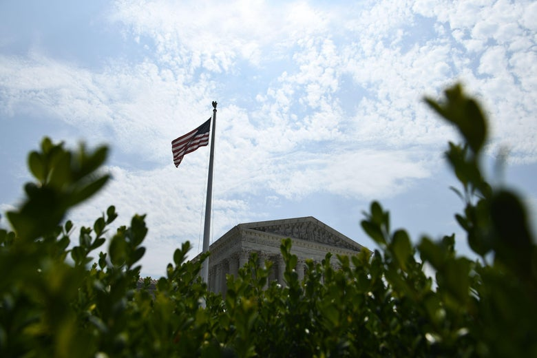 The roof of the Supreme Court and an American flag are viewed above a tree line.