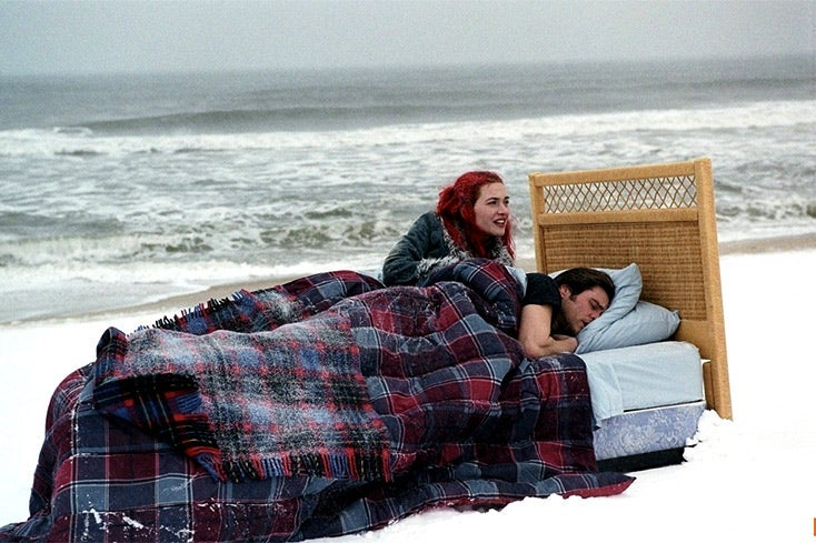 Kate Winslet and Jim Carrey recline in a bed on a snowy beach.