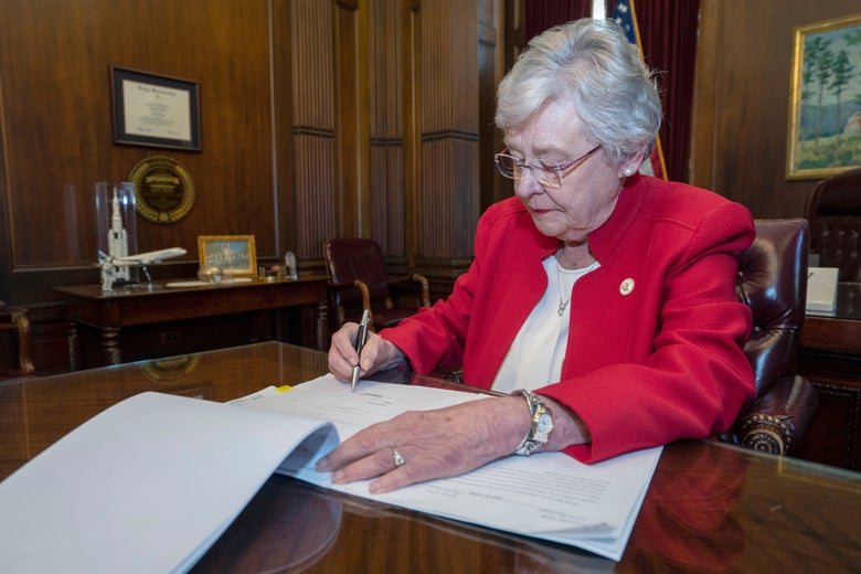 Ivey signing the law on a desk in the governor's office.