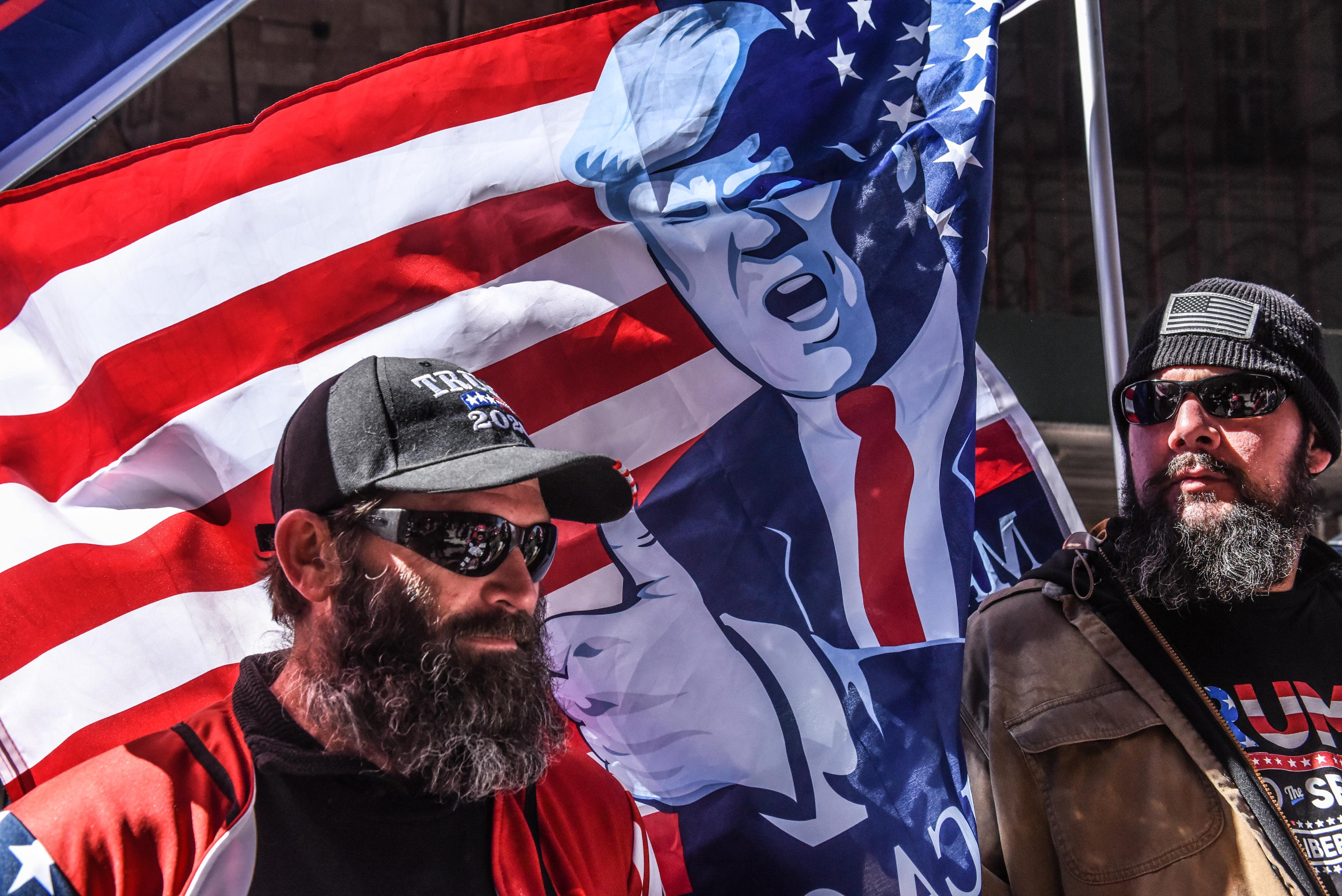 Two men in front of an American flag with Trump on it.